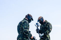 Paintballers standing in battlefield. Paintballer standing in battlefield, in camouflage cloths Stock Photography