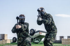 Paintballers standing in battlefield Stock Photo