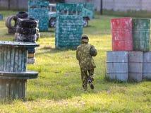 Paintballspelare i kamouflagelikformig och skyddande maskering med vapnet på fältet, skjuter in i fiender i sommaren aktiv sport arkivfoto
