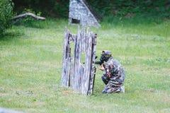 Paintballsportspelare i likformig och maskering med vapnet utomhus Arkivbild