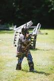 Paintballsportspelare i likformig och maskering med vapnet utomhus Arkivbilder