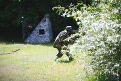 Paintballsportspelare i likformig och maskering med vapnet utomhus Royaltyfri Foto