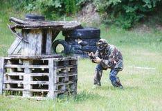 Paintballsportspelare i likformig och maskering med vapnet utomhus Royaltyfria Bilder