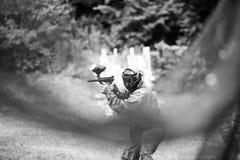Paintballsportspelare i likformig och maskering med vapnet utomhus Royaltyfria Foton