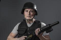 Paintballsportspelare som bär den skyddande hjälmen som siktar pistolen, arkivfoton