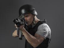 Paintballsportspelare som bär den skyddande hjälmen som siktar pistolen, royaltyfria bilder