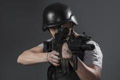 Paintballsportspelare som bär den skyddande hjälmen som siktar pistolen, royaltyfria foton
