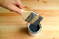 Paintbrush удерживания руки с краской падая после окунать в консервную банку краски на деревянной планке стоковое фото