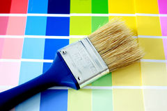 Paintbrush. A blue handled paintbrush against paint manufacturers colour cards stock photos