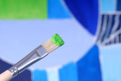 Paintbrush. With green paint on a picture Stock Photo