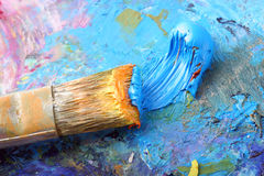 Paintbrush. Bright colored paint with a brush on a palette royalty free stock photography