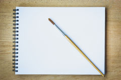 Paintbrush on blank drawing paper book royalty free stock photography