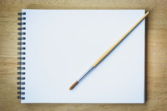 Paintbrush on blank drawing paper book stock images