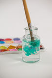 Paintbrush with blue paint dipped into a jar filled with water Stock Photos