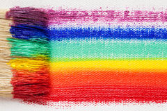 Paintbrush bristle closeup and multicolor rainbow brush strokes. On artist canvas royalty free stock photo