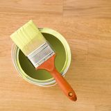 Paintbrush on can. High angle view of paintbrush resting on paint can on wood floor stock photography