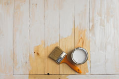 Paintbrush and can lying on partially painted wooden background. Top view. Royalty Free Stock Photos