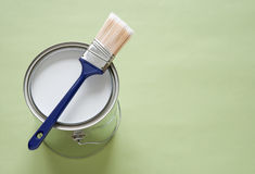 Paintbrush and can of paint on green background. Paintbrush and a newly opened can of white paint on green background Stock Images