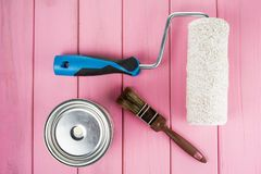 Paintbrush, can of paint and paint roller on a painted pink background stock photo