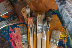 Paintbrush collection on old palette top view. Mixing different oil paints in art studio. Royalty Free Stock Photography