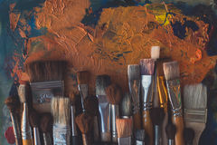 Paintbrush collection on old palette top view. Mixing different oil paints in art studio. Stock Photos