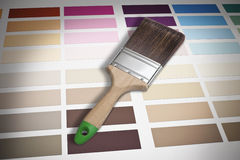 Paintbrush And Color Chart. A paintbrush resting on a color paint chart Stock Photo
