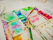 Paintbrush with color tray. On the table stock photo