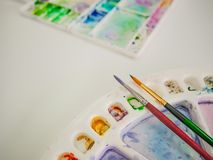 Paintbrush with color tray. On the white table stock images