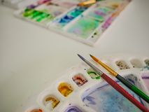 Paintbrush with color tray. On the white table stock photo