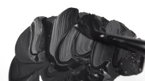 Paintbrush draws black paint on a white canvas with bold strokes.