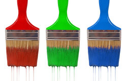A paintbrush dripping with rgb paint. Isolated on white Stock Photo