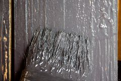 The paintbrush is dyed with a gray paint. The wooden surface is covered with a dark-colored paint royalty free stock photos