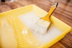 Paintbrush and glue container on concrete surface. Composition tools for home repair and interior renovation indoors royalty free stock images