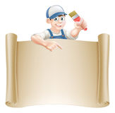 Paintbrush guy and scroll. A painter decorator holding a paintbrush and peeking over a scroll banner and pointing Royalty Free Stock Photography