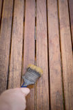 Paintbrush in hand and painting on wooden table Royalty Free Stock Photo
