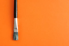 A paintbrush. Isolated on an orange background royalty free stock photos