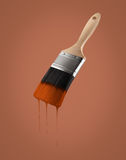 Paintbrush loaded with brown color dripping off the bristles. Paintbrush loaded with brown color dripping off the bristles, on brown background Royalty Free Stock Image