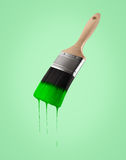 Paintbrush loaded with green color dripping off the bristles. On green background Royalty Free Stock Photography