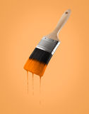 Paintbrush loaded with orange color dripping off the bristles. Royalty Free Stock Photography