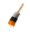 Paintbrush loaded with orange color dripping off the bristles. Stock Photo