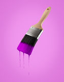 Paintbrush loaded with purple color dripping off the bristles. Stock Photo