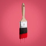 Paintbrush loaded with red color dripping off the bristles. Paintbrush loaded with red color dripping off the bristles, on red background Stock Photography