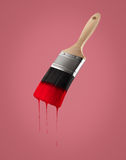 Paintbrush loaded with red color dripping off the bristles. Royalty Free Stock Images