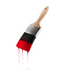 Paintbrush loaded with red color dripping off the bristles. Stock Photos