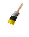 Paintbrush loaded with yellow color dripping off the bristles. Isolated on white background Stock Photography