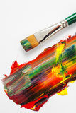 Paintbrush and mixed rainbow oil paints on artist canvas Royalty Free Stock Photos