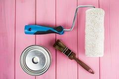 Paintbrush, może farba i farba rolownik na malującym różowym tle zdjęcie stock