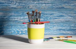 Paint brush in the mug. Paintbrush in mug in front of a rustic, blue wall in the background Royalty Free Stock Images
