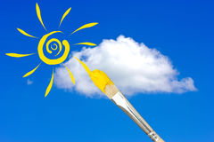 Paintbrush painting the sun in a sky. Paintbrush painting the yellow sun in a blue sky Royalty Free Stock Photography