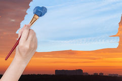 Paintbrush paints blue day sky on orange sunset Stock Photos